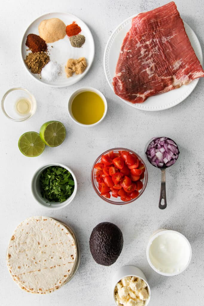steak taco ingredients in bowls, ready to be mixed together for steak tacos