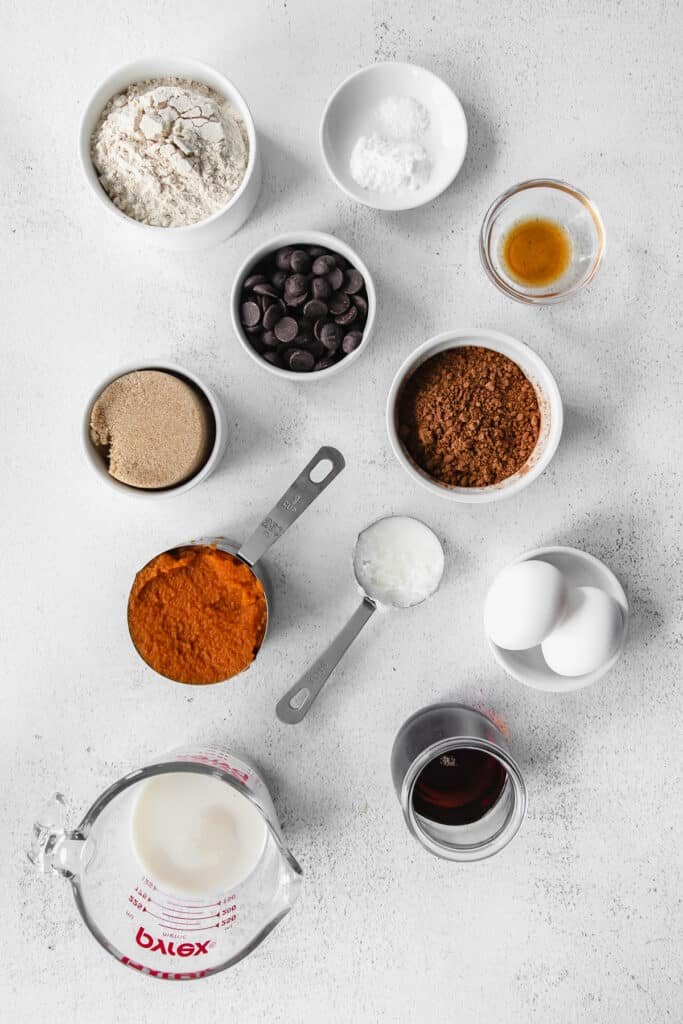 All the ingredients for pumpkin bread in small bowls.