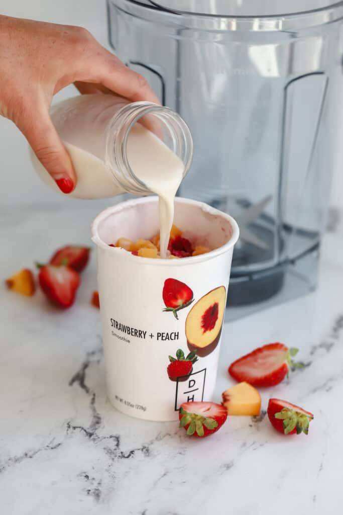 milk being poured in a smoothie cup before being put in a blender