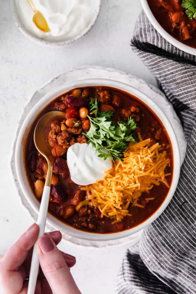 instant pot chili in a bowl topped with shredded cheese greek yogurt and fresh parsley